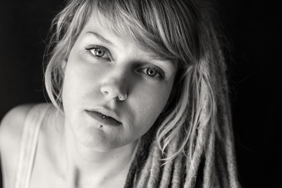 Eine junge Frau mit Dreadlocks und Lippen- und Nasenpiercing schaut in die Kamera.