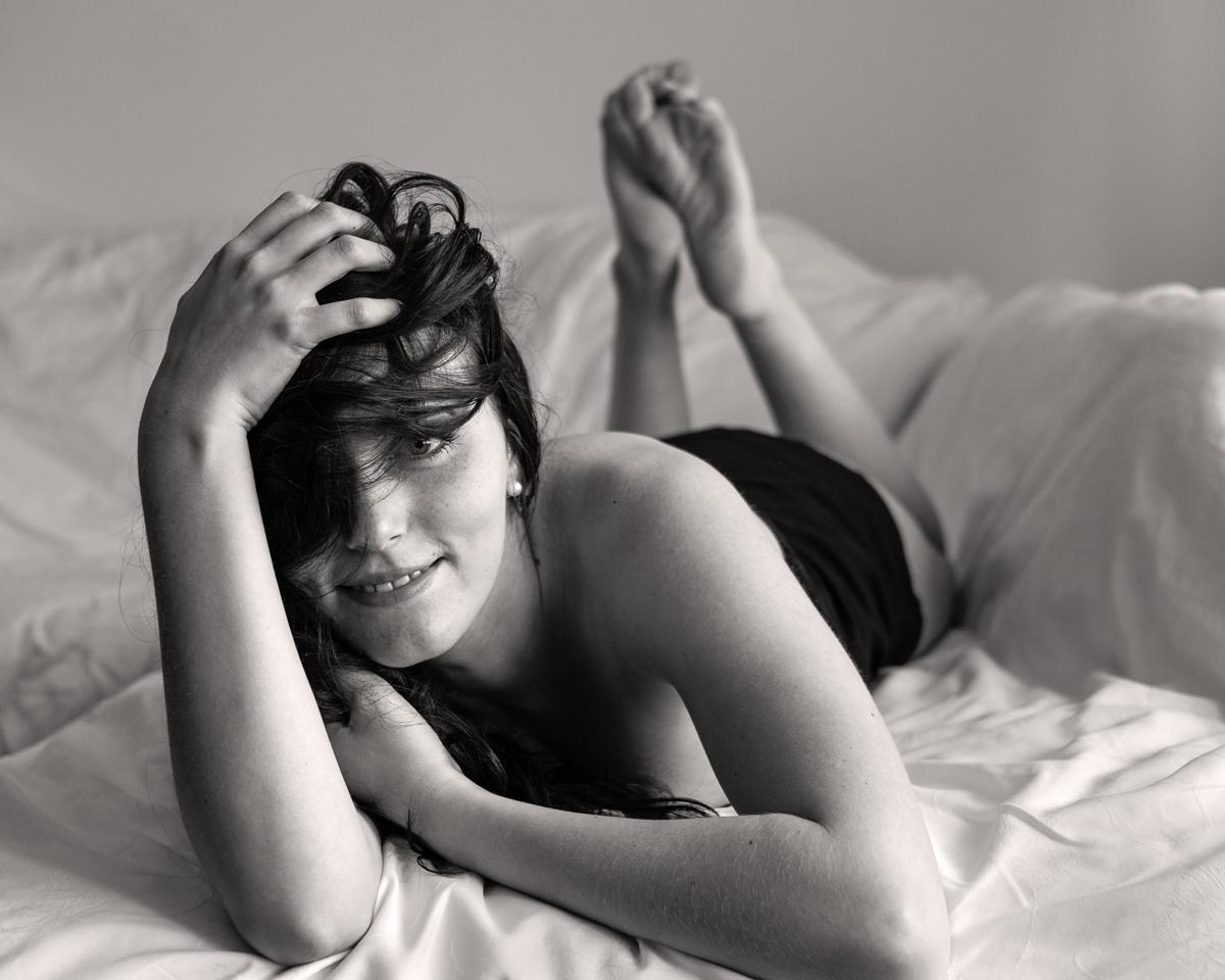 Sinnliches Portrait einer jungen Frau, die sich auf einem Laken räkelt. Fotografin: Astrid Schulz, Bremen.
