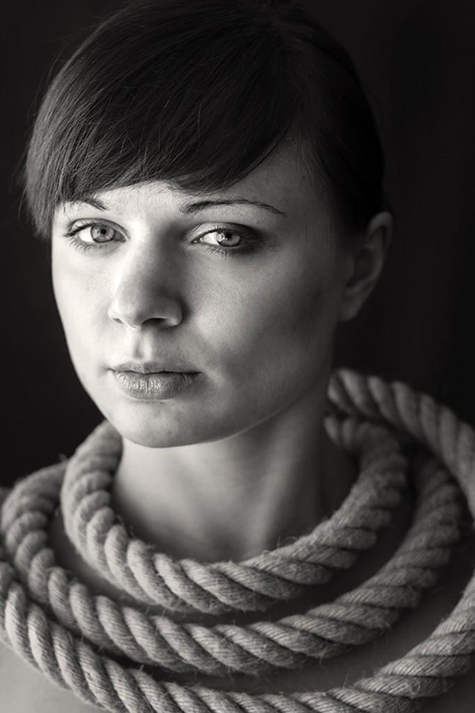 Portrait einer dunkelhaarigen Frau. Sie hat ein dickes Seit kunstvoll um ihren Hals drapiert.