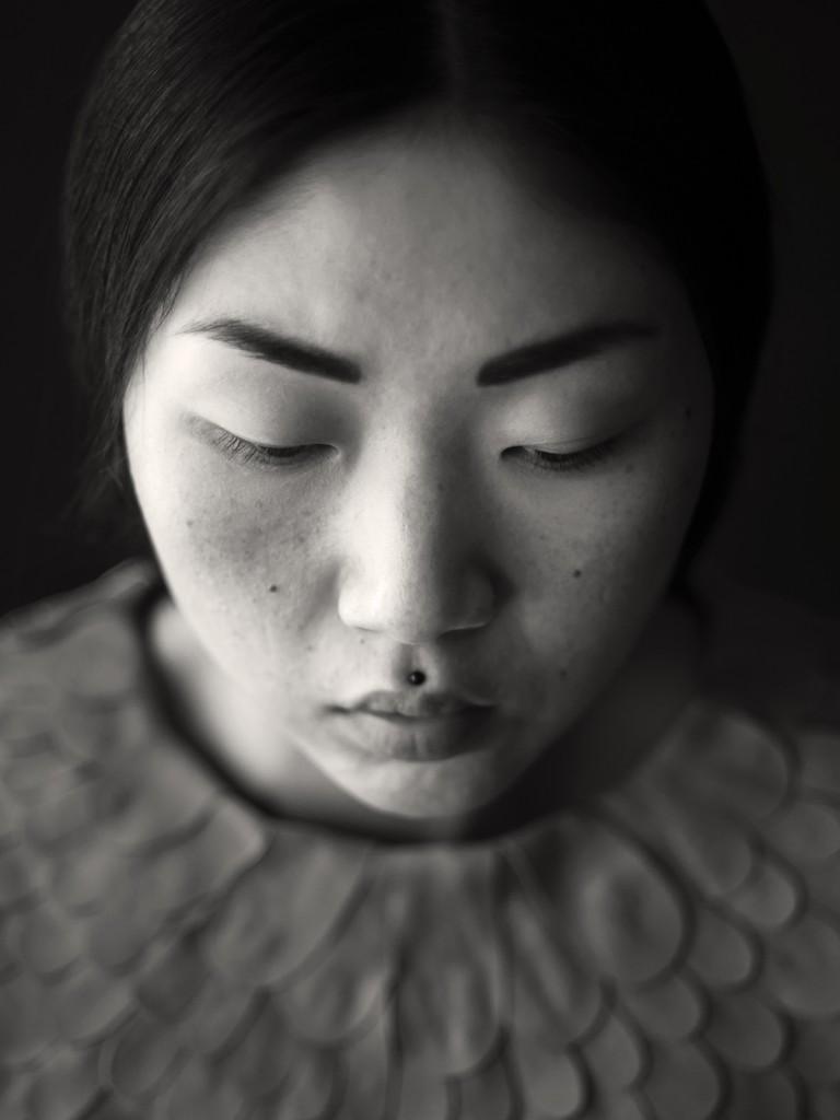 Portrait einer Asiatin in schwarz-weiß. Sie hat ihren Blick gesenkt.