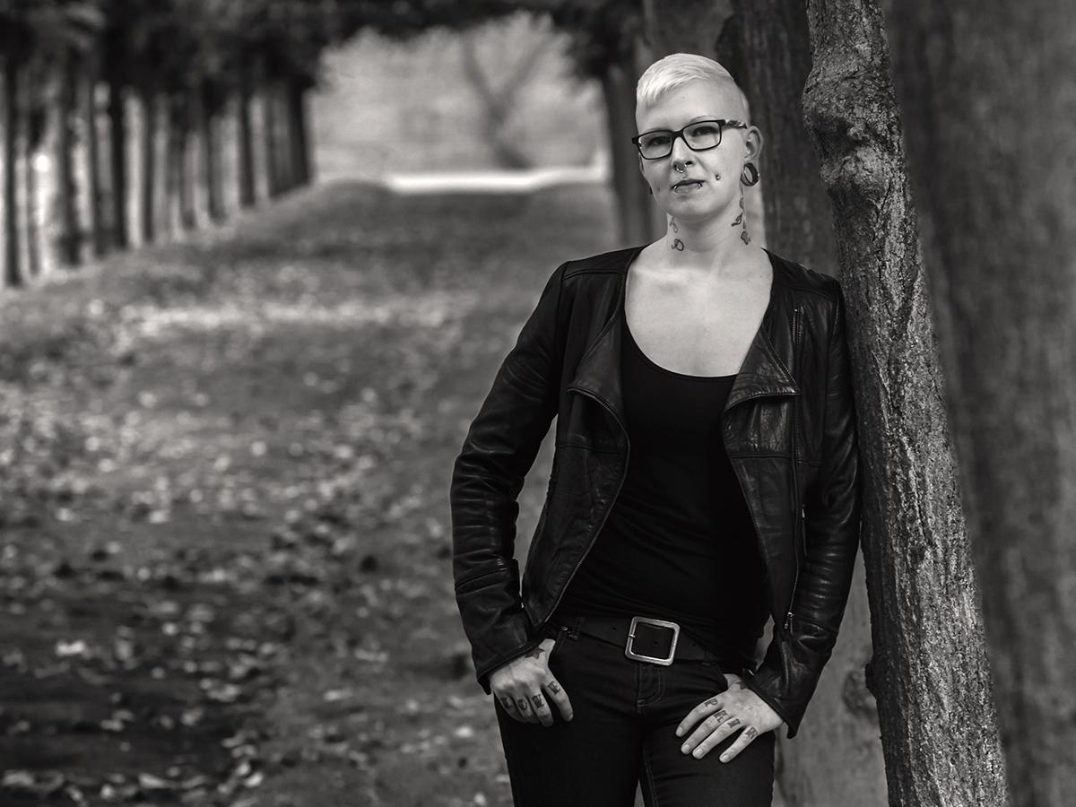 Eine blonde Frau mit Sidecut-Haarschnitt und Brille lehnt an einem Baum.