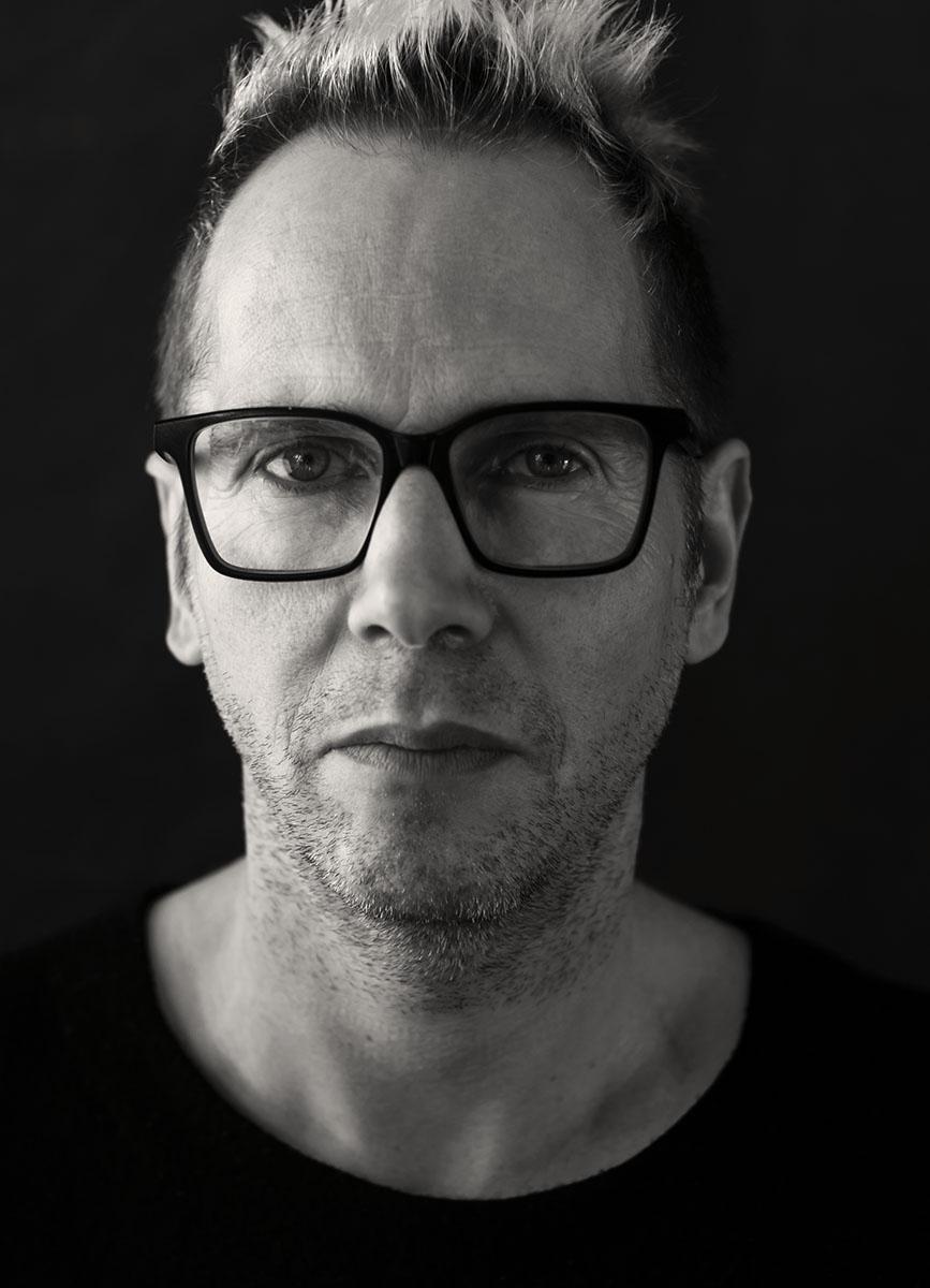 Schwarzweißportrait eines Mannes. Der Mann trägt eine Brille.