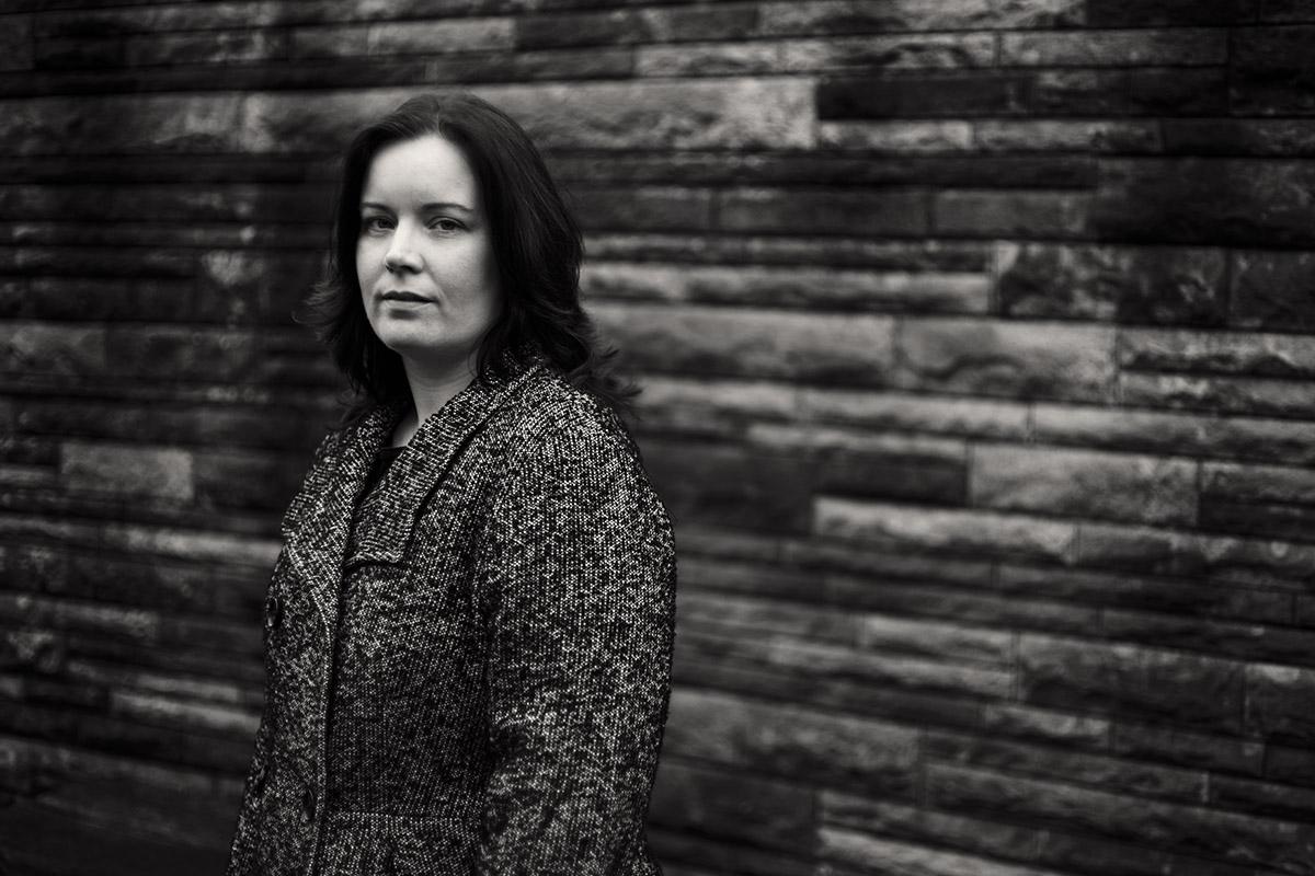 Portrait einer dunkelhaarige Frau im Pfeffer-Salz-Mantel. Fotograf: Astrid Schulz aus Bremen.