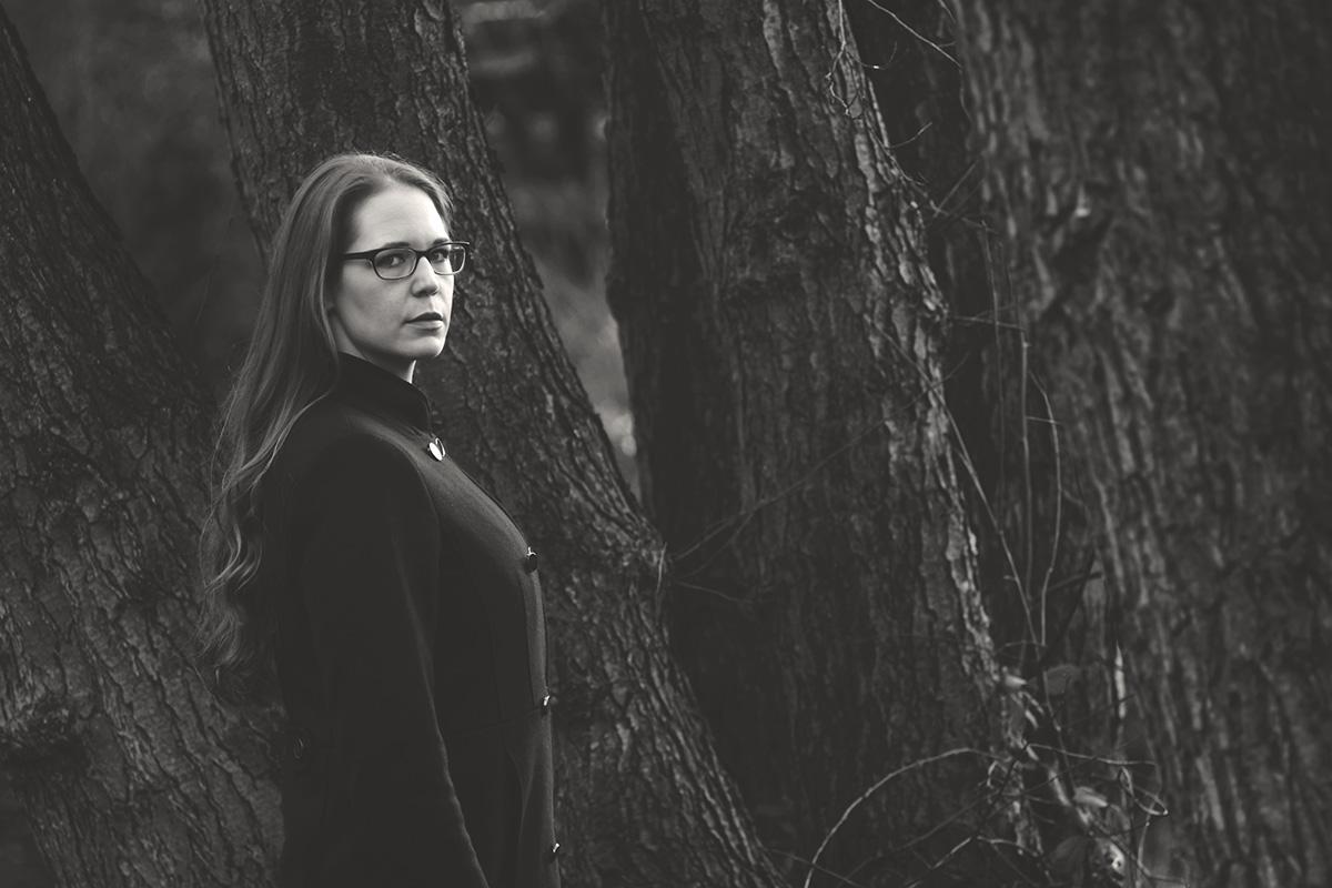 Zwischen Bäumen sieht man eine Frau. Die um die 30 Jahre alte Daniela wurde fotografiert von Fotografin Astrid Schulz aus Bremen.