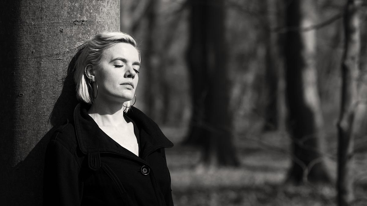 Eine blonde Frau lehnt an einem Baumstamm. Sie genießt die letzten Sonnenstrahlen des Herbst. Schwarz-weiß-Fotografie
