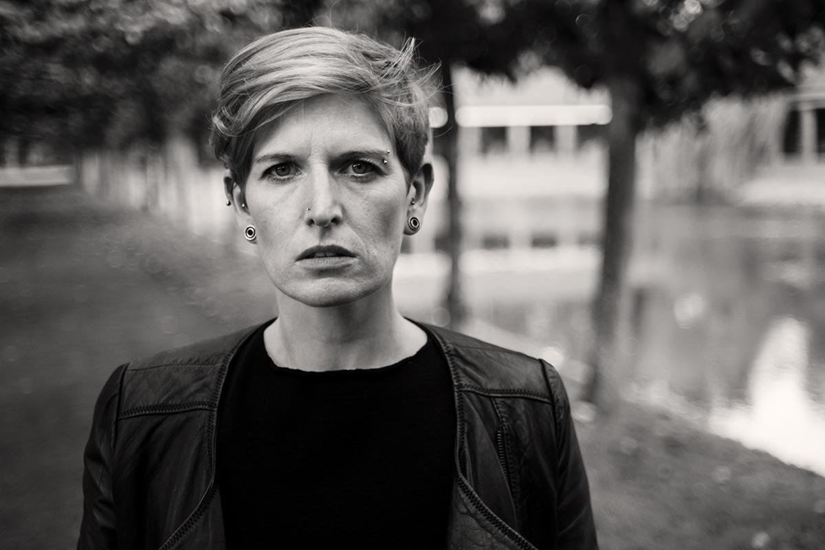 Schwarzweiss Portrait von Andrea. Sie steht in einer Baumallee, hinter ihr sieht man verschwommen einen See und ein Gebäude.