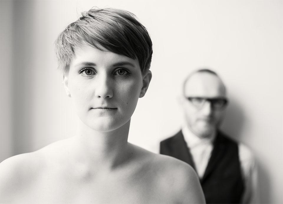 Paarportrait. Die Frau Malena steht im Vordergrund. Hinten an der Wand lehnt Arta, ihr Mann. Er ist nicht scharf zu erkennen. Schwarz-weiß-Aufnahme von Astrid Schulz aus Bremen.