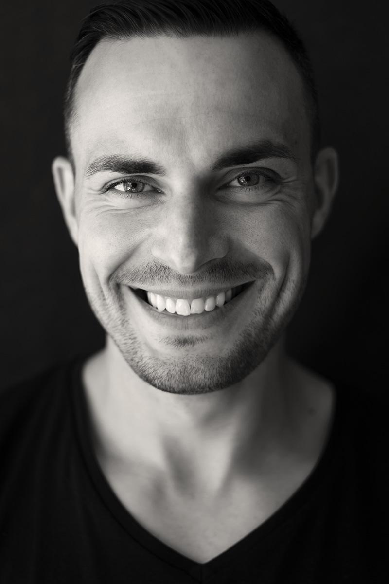 Schwarz-weiß-Portrait eines lachenden Mannes. Fotograf: Astrid Schulz aus Bremen.