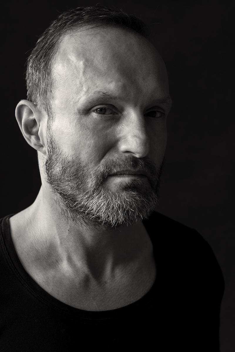 Intensives Schwarz-weiß-Portrait eines Mannes, der direkt in die Kamera blickt.