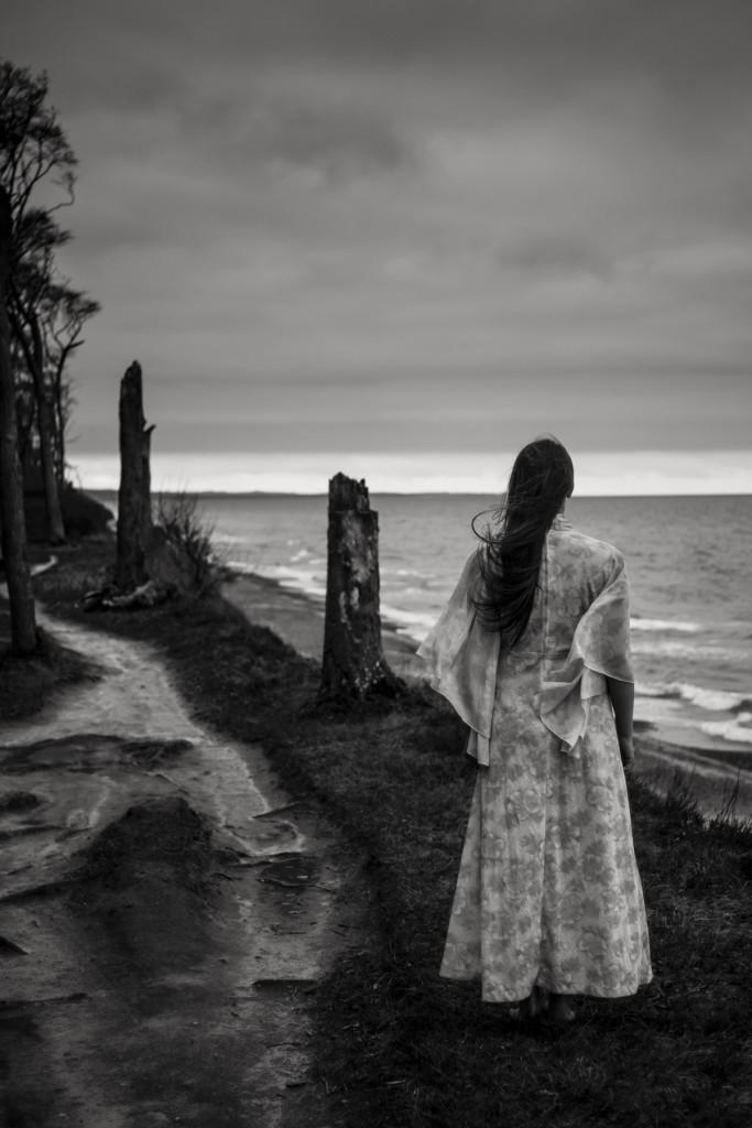 Eine junge Frau  steht mit dem Rücken zu uns. Sie steht an einer Steilküste und blickt in die Ferne. Ihr langes Haar und ihr Kleid wehen im Wind. Fotografin ist Astrid Schulz aus Bremen.