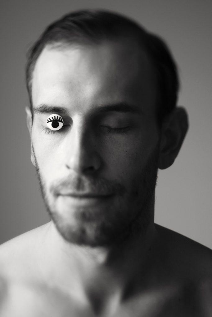Portrait eines Mannes in schwarz-weiß. Seine Augen sind geschlossen. Auf seinem rechten Auge ist eine Auge mit Wimpern geklebt. Fotografin Astrid Schulz aus Bremen.