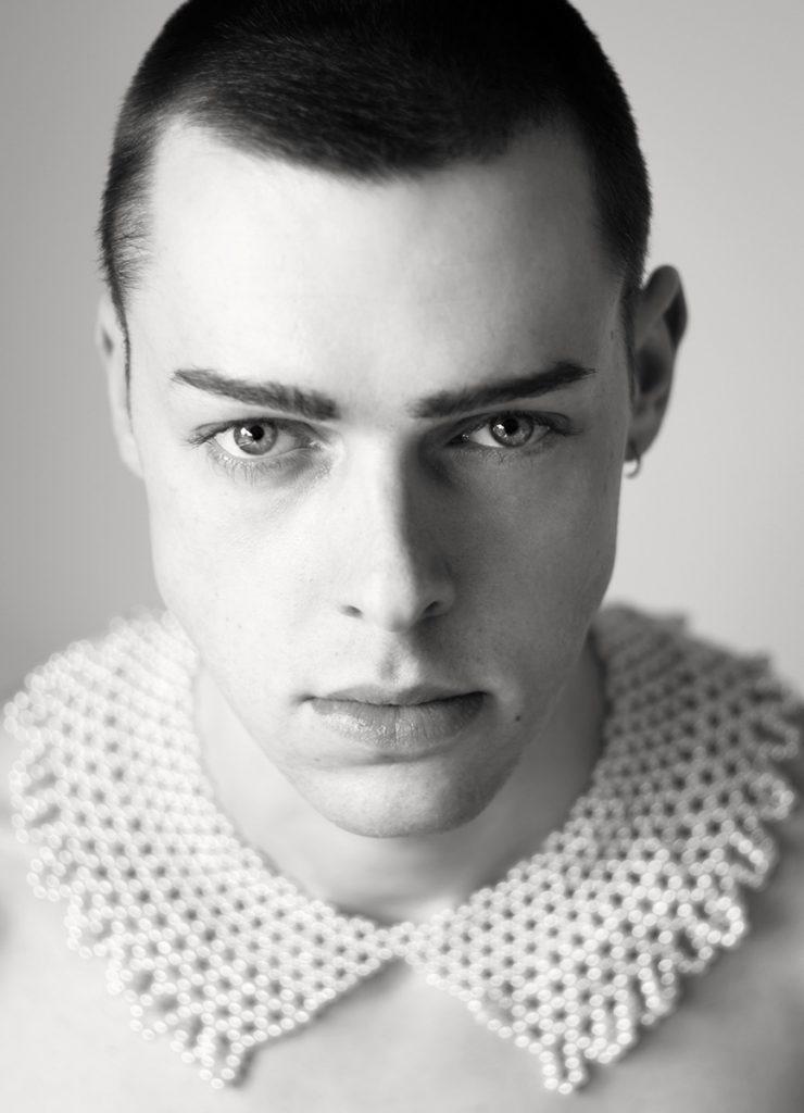 SW-Portrait von dem Mitte 20jährigem Marcel. Er trägt als besonderes Accessoire einen Perlenkragen. Fotografin ist Astrid Schulz aus Bremen.