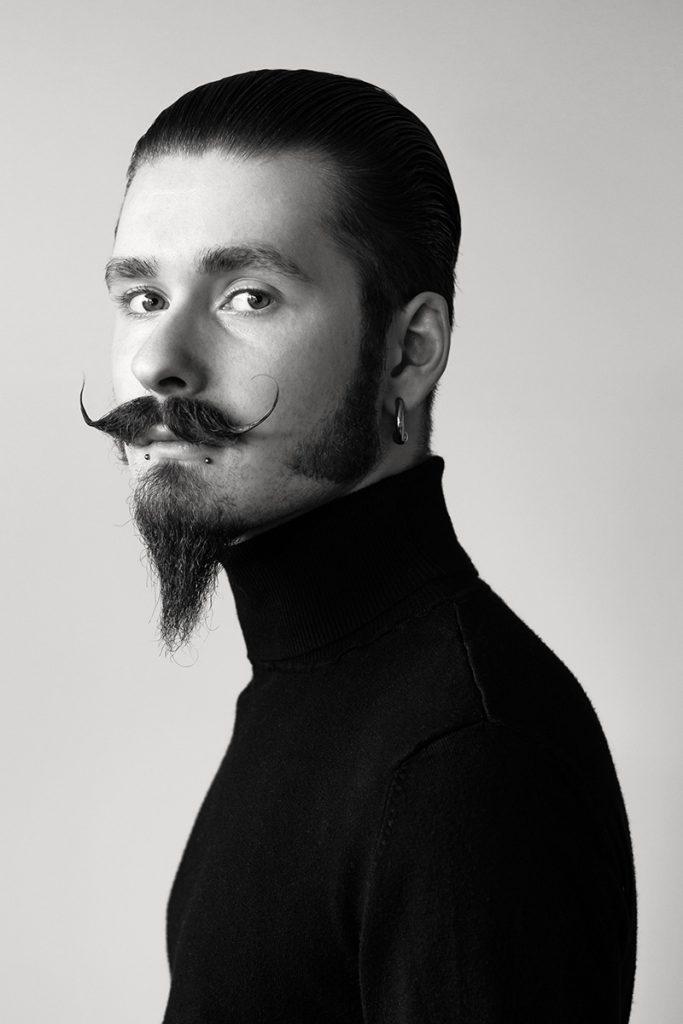 Portrait von Maximilian. Er trägt Bart: einen gezwirbelten Schnäuzer, einen Kinnbart und seitlich verlängerte Koteletten. Aufgenommen von Fotografin Astrid Schulz aus Bremen.