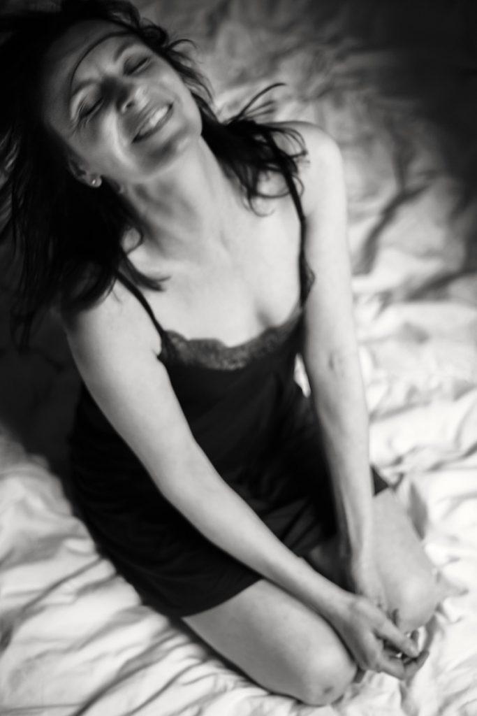 Eine Frau im Negligee wirft lachend ihren Kopf zurück. Das Bild strahlt eine unbändige Lebenslust aus. Fotograf: Astrid Schulz, Bremen.