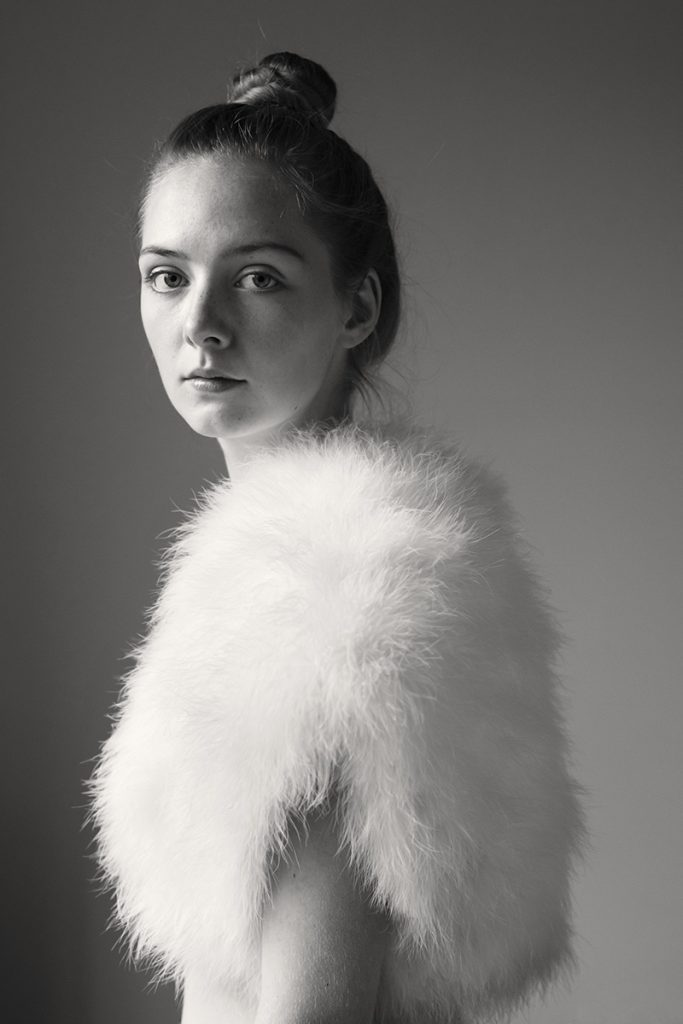 Portrait einer  jungen Frau mit Sommersprossen. Ihre Haare trägt sie zum Dutt, sie trägt eine weiße Federweste.