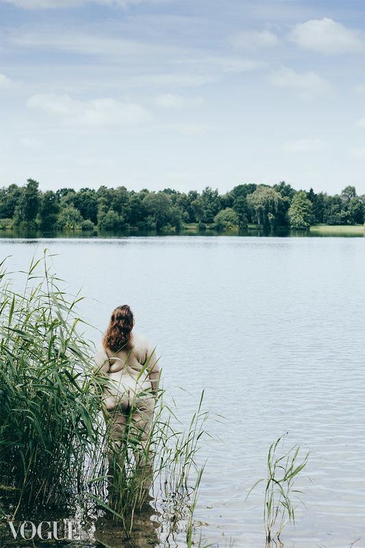 Wir sehen eine Frau im See stehen. Ihre Unterschenkel sind bis zur Hälfte mit Wasser bedeckt. Sie kehrt uns den Rücken zu. Der Himmel ist blau und voller Wölkchen.