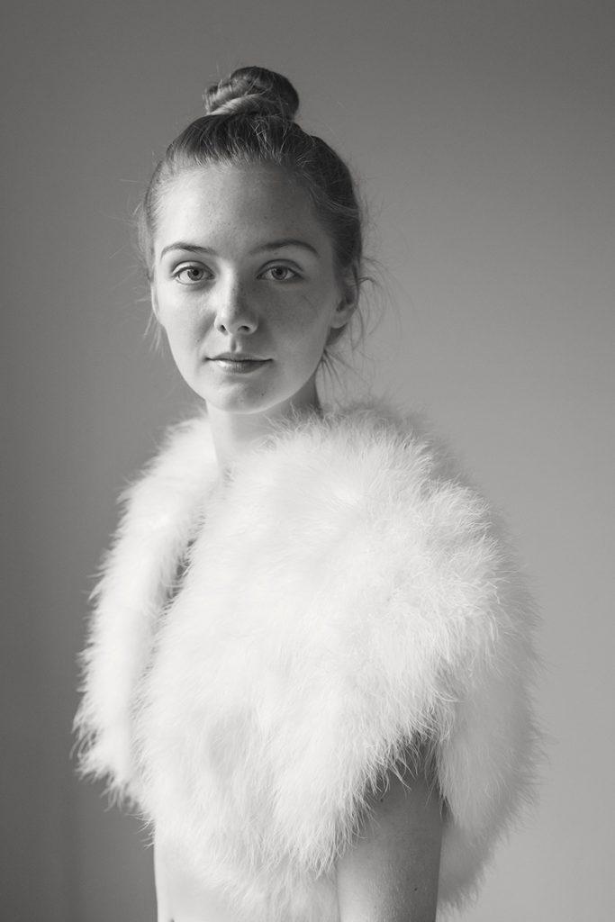 Schwarz-weiß Porträt einer jungen Frau. Sie blickt vertrauensvoll in die Kamera. Durch die Weste, die aus Federn besteht, wirkt sie wie ein Küken. Aufgenommen von Fotografin Astrid Schulz aus Bremen.