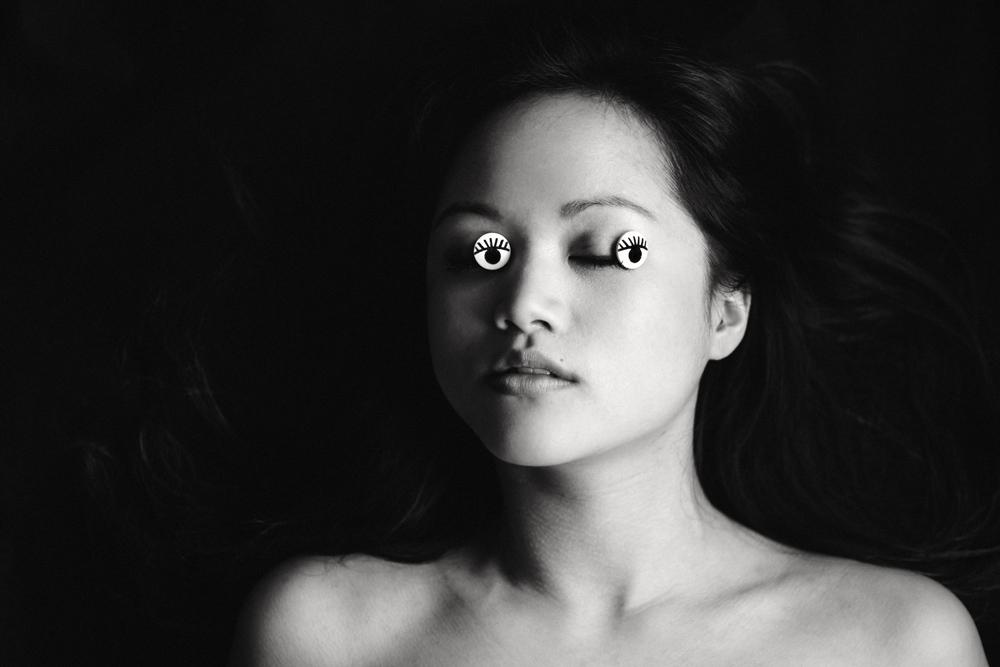 """Eine junge Frau liegt auf dem Boden, ihre schwarzen langen Haare glänzen. Die Augen hat sie geschlossen. Auf den geschlossenen Lidern liegen """"Augen"""". Fotografin / Künstlerin: Astrid Schulz, Bremen."""