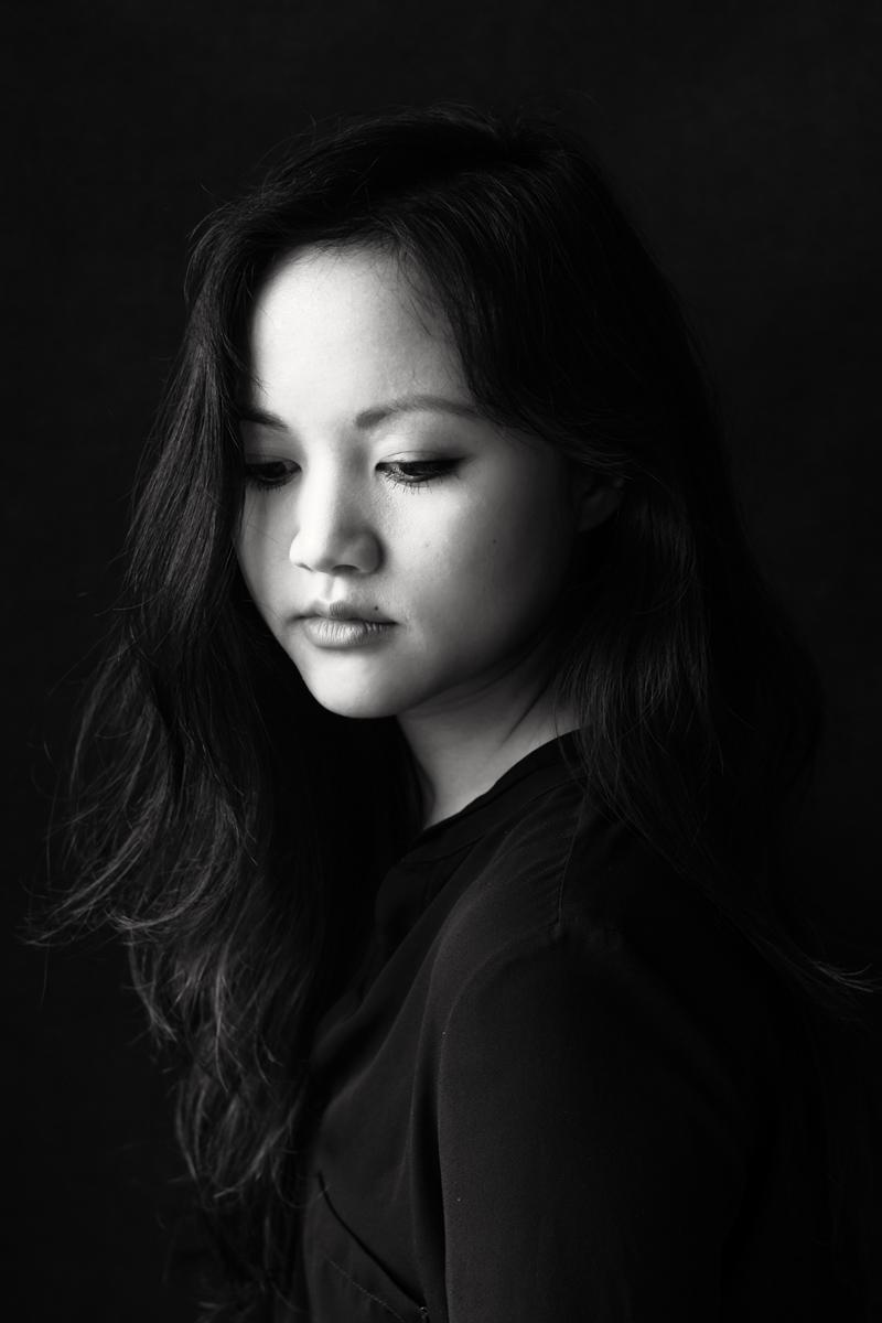 Portrait einer Asiatin. Sie hat lange, dunkle Haare und blickt nachdenklich auf den Boden. Fotografin Astrid Schulz aus Bremen.