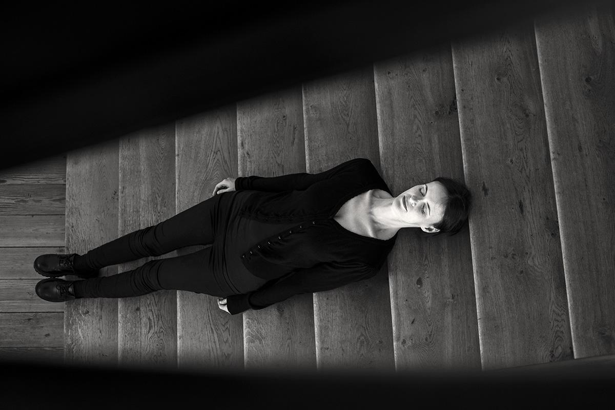 Schwarz-weiß-Fotografie. Eine Frau liegt auf Holztreppe. Ihre Augen sind geschlossen.