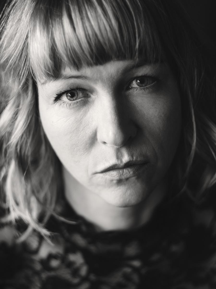 Portrait einer blonden Frau. Sie sieht ernst und intensiv in die Kamera.