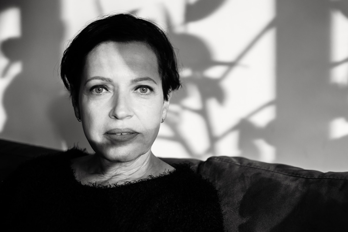 Porträt der Mitte 50jährigen Mirjam. Sie sitzt in meinem Wohnzimmer, wir unterhalten uns. Die Abendsonne scheint durch das große Fenster. Die Schatten auf ihrem GEsicht finde ich spannend und fotografiere sie. Fotografin: Astrid Schulz aus Bremen.