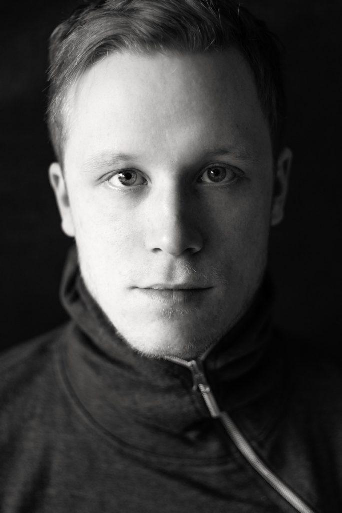 Charakterporträt eines Mitte 20jährigen, jungen Mannes. Der blonde Justin blickt intensiv in die Kamera von Fotografin Astrid Schulz aus Bremen.