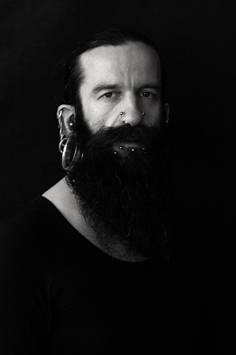 Oliver, ein Mann mit vielen Piercings - und Haaren! Charakterporträt von Fotografin Astrid Schulz aus Bremen.