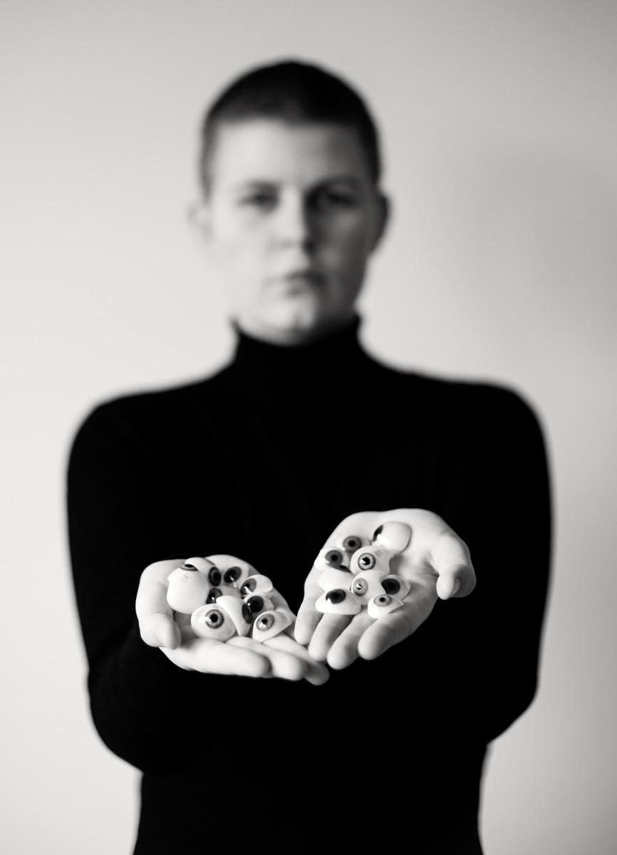 Glasaugen liegen in ihren Händen und blicken uns an. Fotografie von Astrid Schulz aus Bremen.