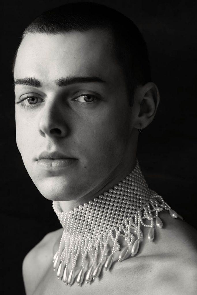"""Portrait aus der Serie """"Portrait mit Perlenkette"""". Marcel trägt eine eng anliegende Perlenkette um den Hals. Aufgenommen von Fotografin Astrid Schulz, Bremen."""