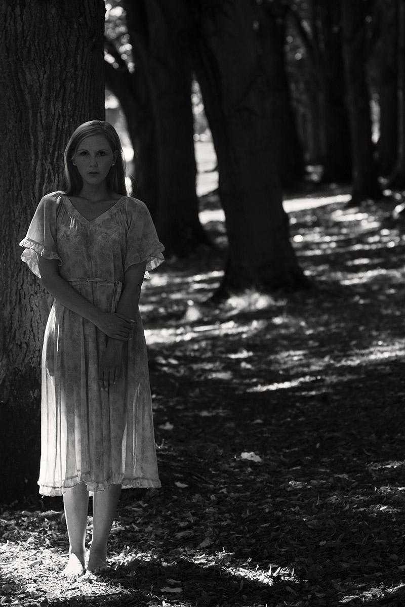 Schwarz-weiß-Foto: Eine junge Frau im Sommerkleid steht im Wald. Die Sonne scheint durch die Bäume.