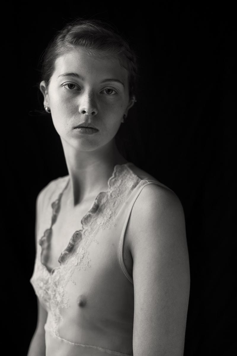 Eine junge Frau ist mit einem durchsichtigen, hellen Oberteil bekleidet. Sie blickt träumerisch in die Kamera.