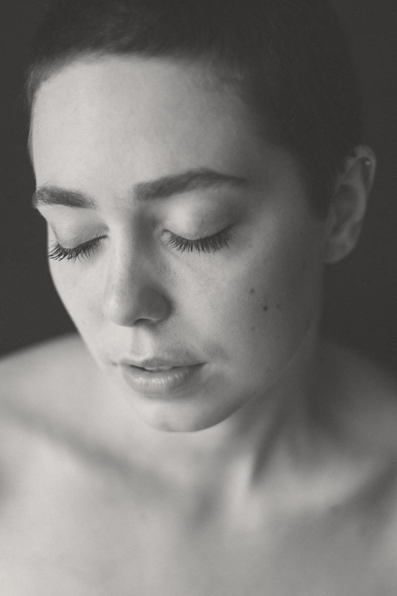 Schwarzweiß-Porträt einer jungen Frau. Sie hat die Augen geschlossen.