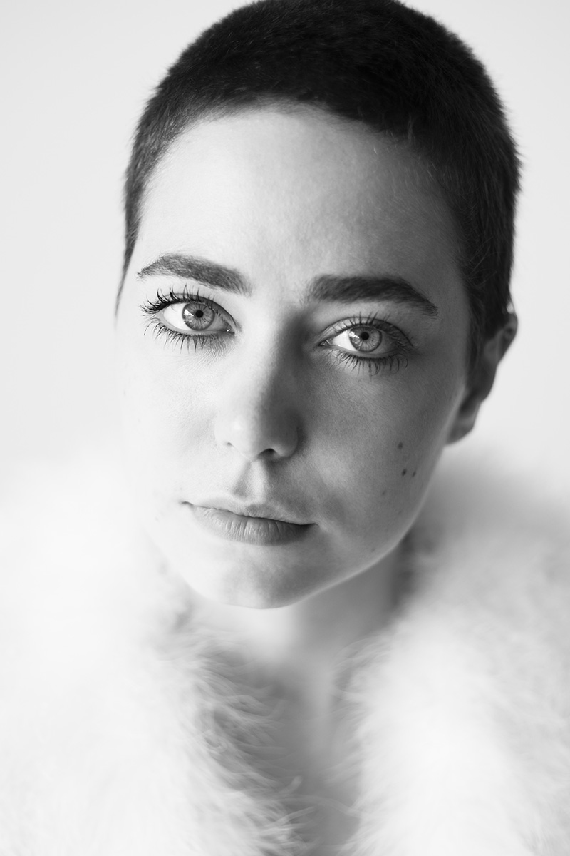 Eine Frau Anfang 20, mit Pixieschnitt, schaut direkt in die Kamera. Ihre hellen Augen leuchten.