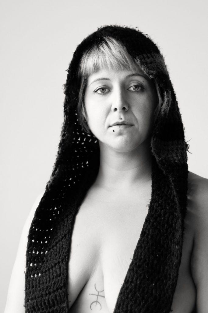 Bonnie trägt einen Schal, der gleichzeitig eine Mütze ist. Die Enden des Schals verdecken ihre Brüste. Sie wirkt auf den Betrachter wie eine Madonna. Fotografin: Astrid Susanna Schulz aus Bremen.