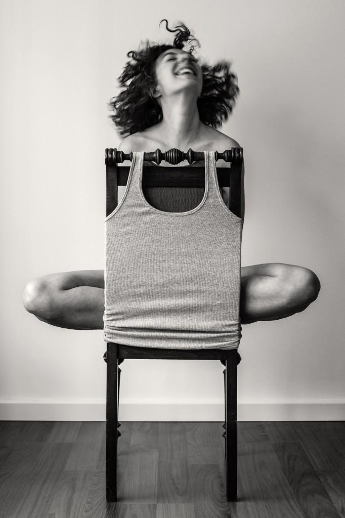 Eine Frau sitzt im Schneidersitz rücklings auf einem Stuhl. Die Lehne verdeckt ihren Körper. Sie schüttelt ihre Haare.