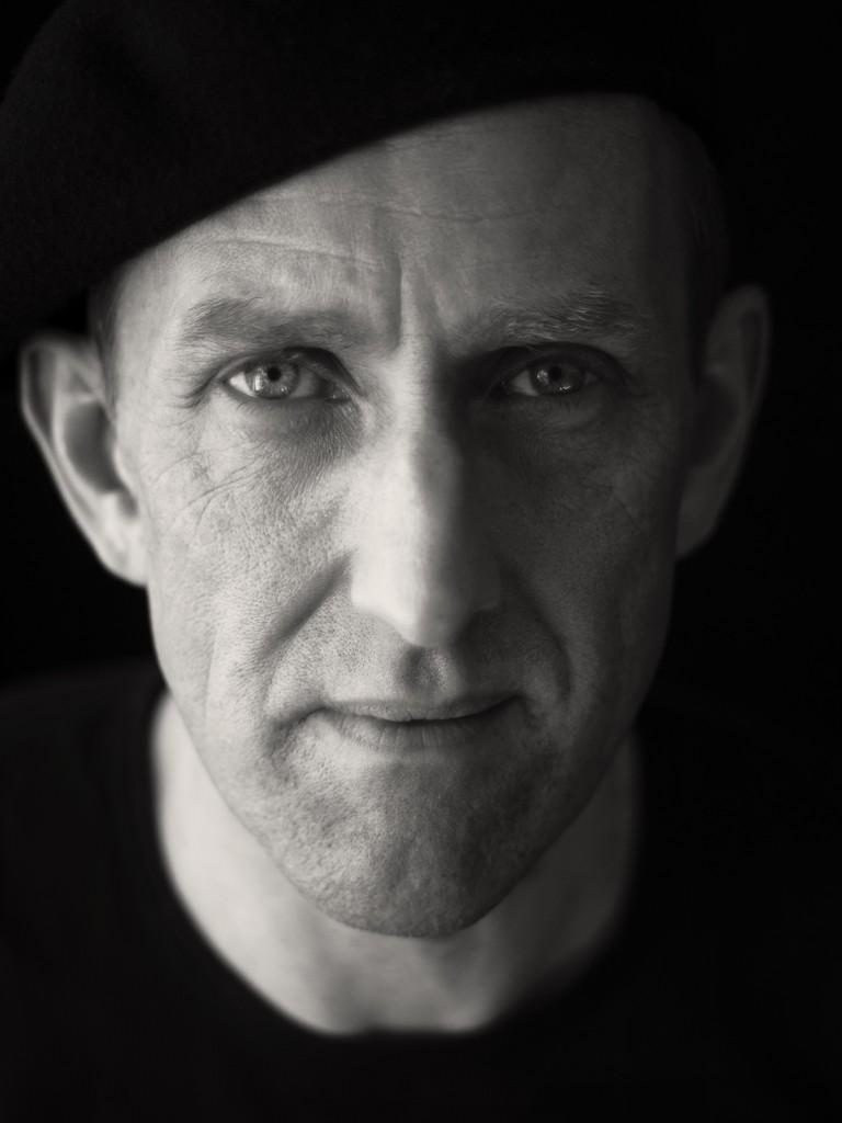 Schwarz-weiss-Portrait eines Mannes mit Baskenmütze.