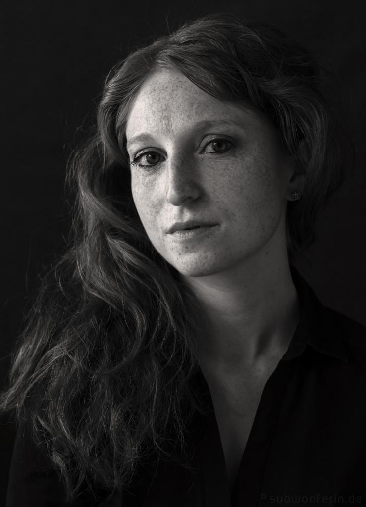 Ein Portrait einer Frau mit vielen Sommersprossen. Schwarz-Weiss-Fotografie.