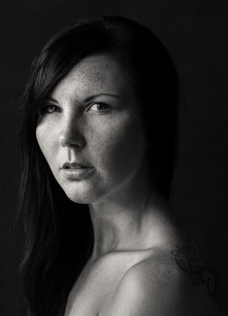 Portrait von Anni. Sie hat lange schwarze Haare und Sommersprossen. Fotografin: Astrid SChulz aus Bremen.