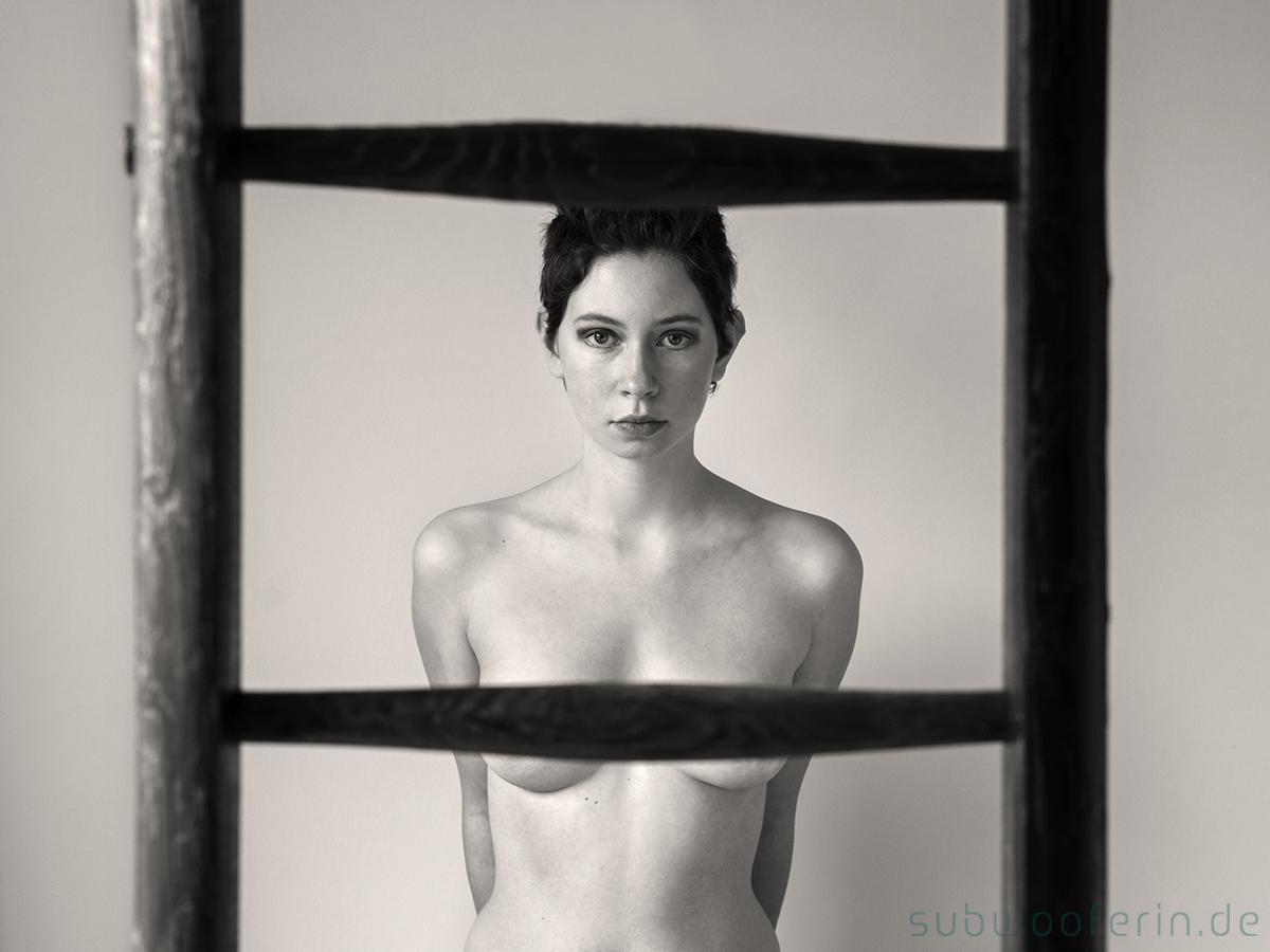 Im Vordergrund steht eine Holzleiter. Dahinter sieht man eine junge, nackte Frau. Ihre Brüste sind durch die Leiterstufen verdeckt. Aktportrait von Fotografin Astrid Schulz aus Bremen.